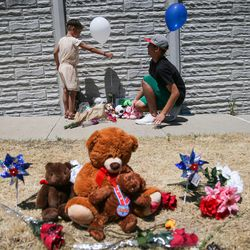 Ava Linsenmeyer, 5, and her brother, Nicholas Tellez, 18, place balloons at a memorial to the victims of Tuesday's fatal shooting on Alta Canyon Drive in Sandy on Wednesday, June 7, 2017. Linsenmeyer was a kindergarten classmate of Jase Rackley, who was killed in the shooting.