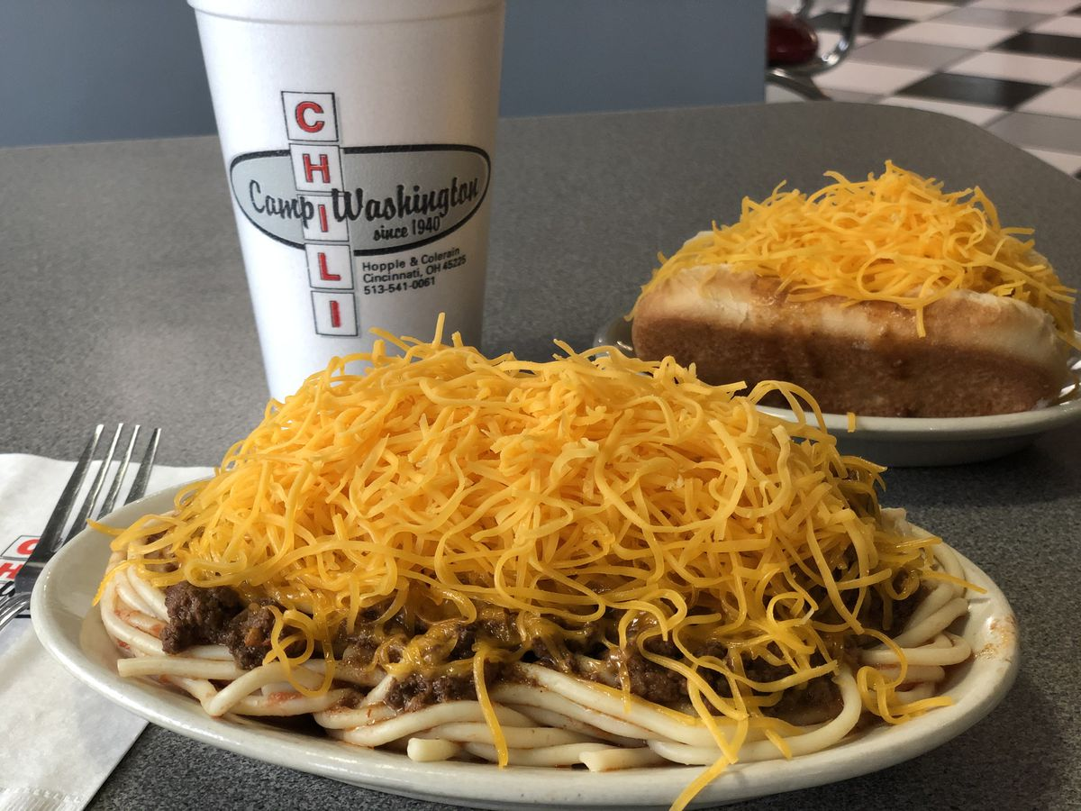 A plate of spaghetti topped with chili and cheese, a chili dog topped with cheese in the background, and a soda in a branded cup on a diner table