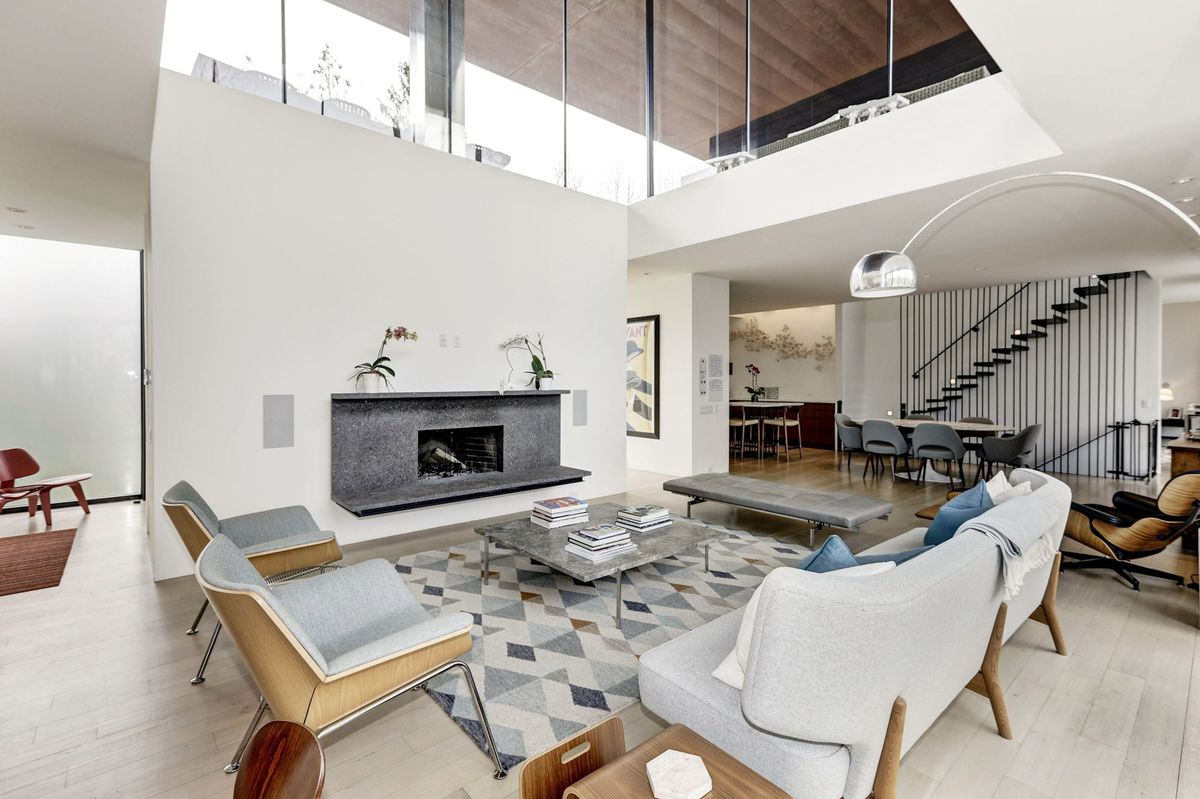 A living room with a glass cube sunlight, gray fireplace, and contemporary furniture.