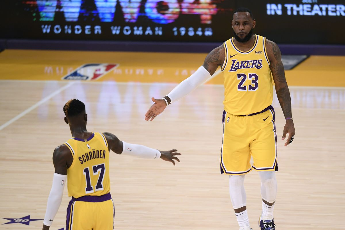 LeBron James of the Los Angeles Lakers celebrates a play with Dennis Schroder during a 116-109 LA Clippers win in the season opening game at Staples Center on December 22, 2020 in Los Angeles, California.