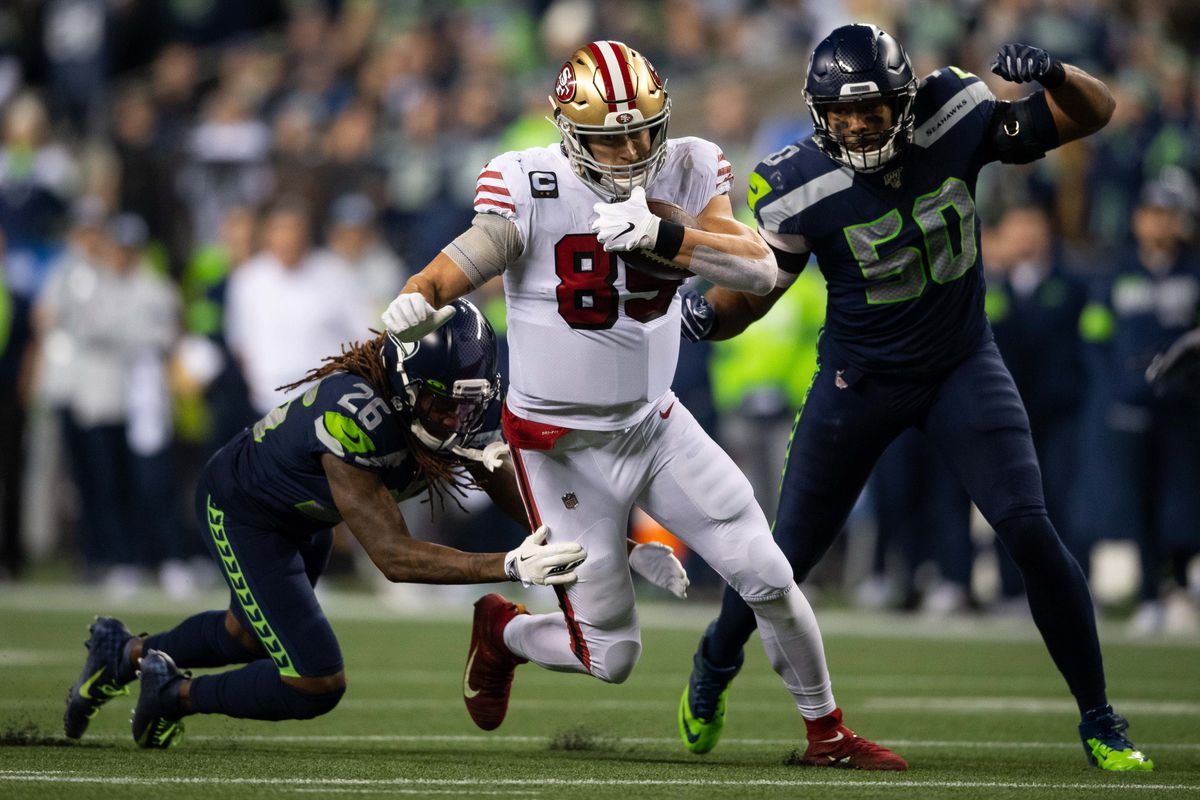 San Francisco 49ers tight end George Kittle carries the ball while being defended by Seattle Seahawks cornerback Shaquill Griffin and Seattle Seahawks outside linebacker K.J. Wright during the first half at CenturyLink Field. San Francisco defeated Seattle 26-21.