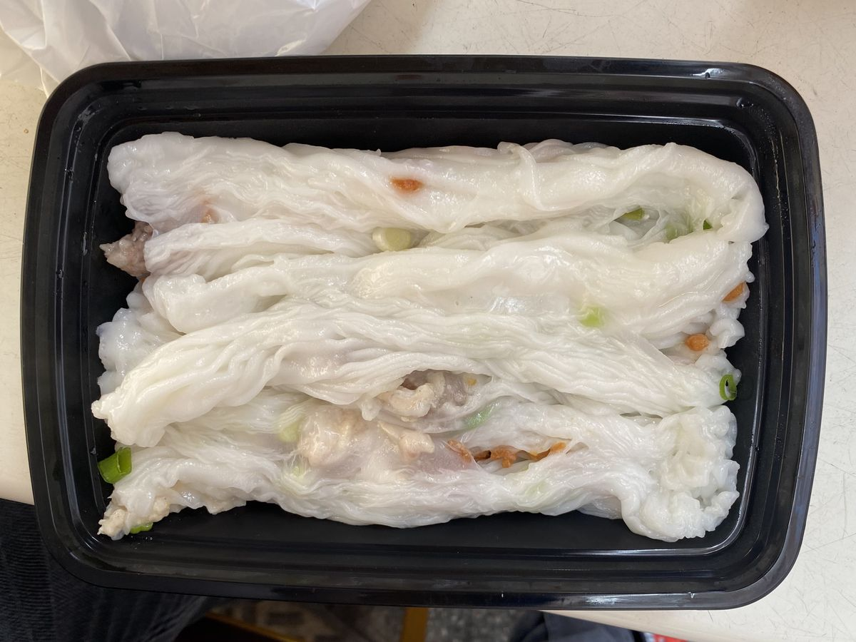 White cheung fun noodles sit in a black plastic takeout container