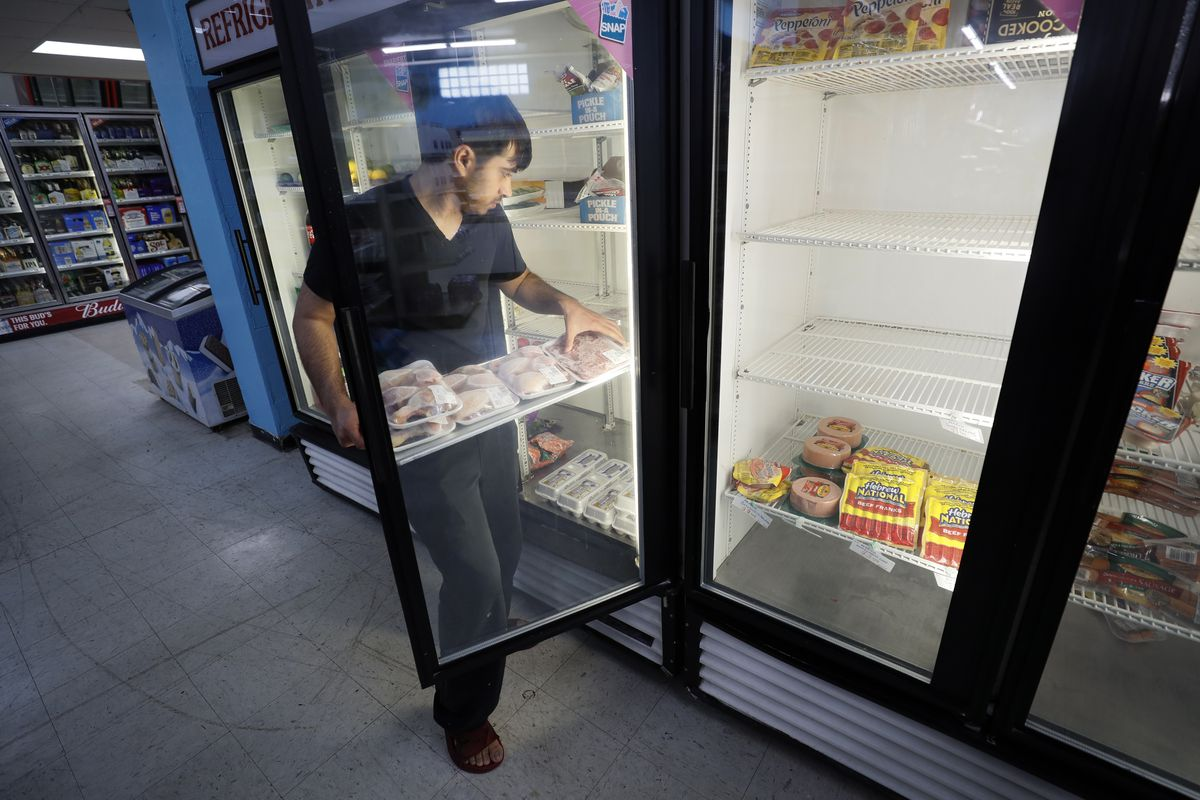 Hardik Kalra stocks meat in a cooler at a local super market, Friday, May 29, 2020, in Des Moines, Iowa.