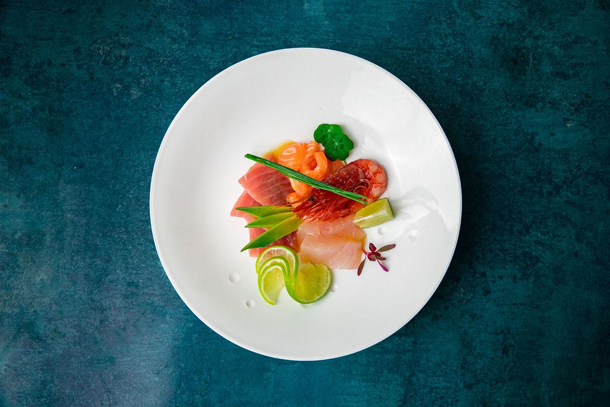 A plate of red prawns, salmon, and tuna with spring onion and cucumber on a white plate on a blue background