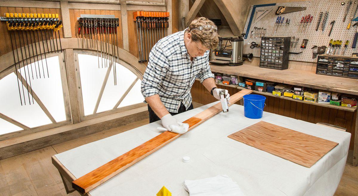 Pessoa a aplicar acabamento ao painel de madeira.