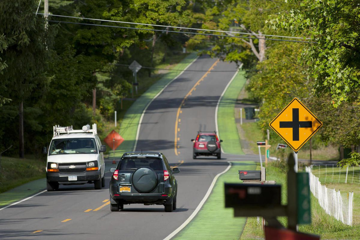 In this Sept. 11, 2012 photo, cars travel along Ellis Hollow Road in Dryden, N.Y., in Tompkins County, where the shoulders of the road are painted green in an attempt to slow down speeding drivers. When the road was repaved in 2011, state regulations requ