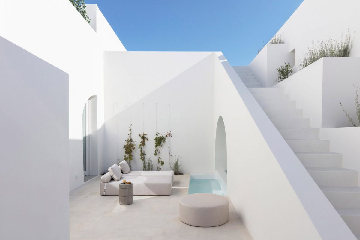 An interior courtyard of a white building featuring outdoor seating next to a small pool.