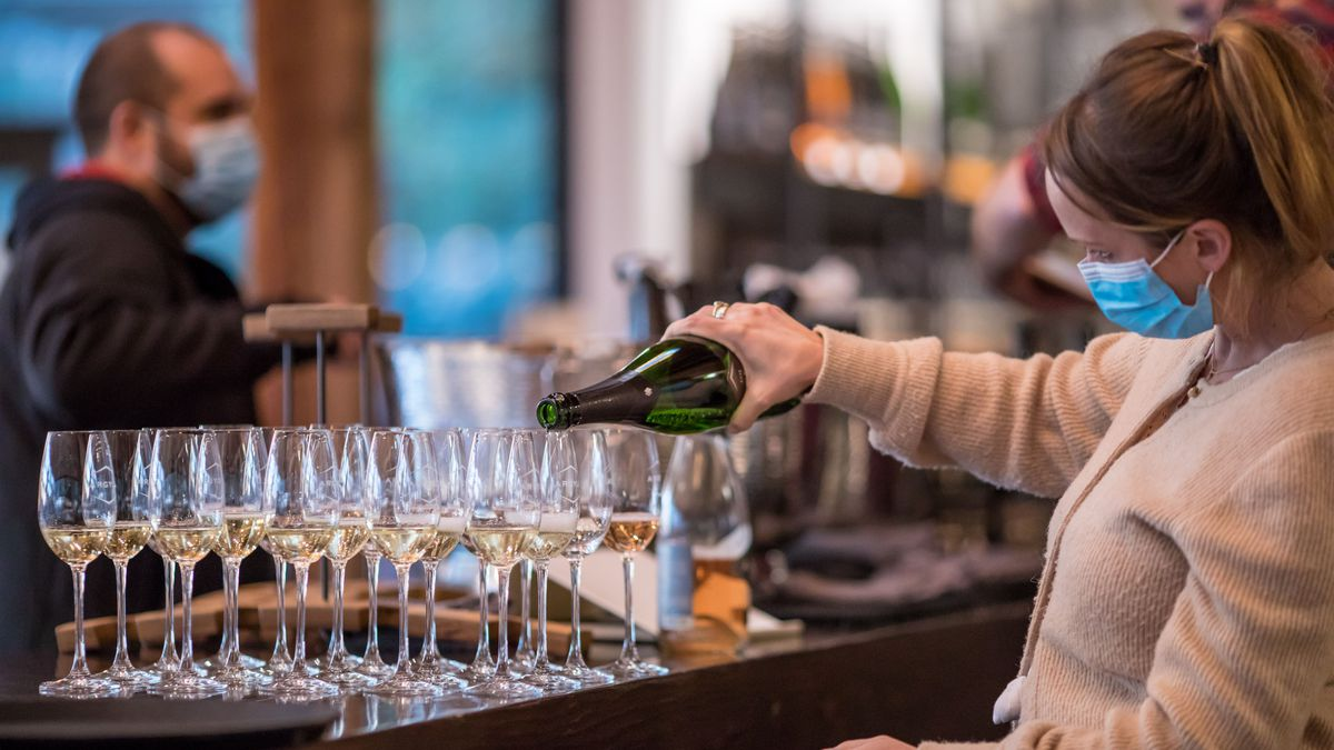 A woman in a blue medical mask and light brown sweater pours sparkling wine into a series of Champagne flutes