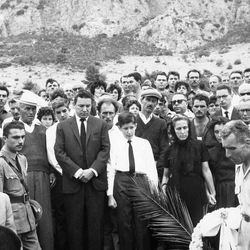 """FILE - In this Sept. 13, 1962 file photo, Mike Wallace stands before his son Peter's grave as the casket is lowered at Kamari Village, Peloponnesus, Greece, after Peter Wallace fell to his death in a accident while climbing a steep mountain in Greece. Behind Wallace is his stepson Andrew, and next to him is his son, Chris, 14, with his mother, Norma Leonard, now Mrs. Bill Leonard, and Mrs. Lorraine Wallace. Wallace, the dogged, merciless reporter and interviewer who took on politicians, celebrities and other public figures in a 60-year career highlighted by the on-air confrontations that helped make """"60 Minutes"""" the most successful primetime television news program ever, has died. He was 93. (AP Photo, File)"""