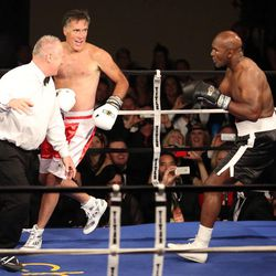Former Massachusetts Gov. Mitt Romney runs away from five-time heavyweight champion Evander Holyfield during Charity Vision Fight Night at The Rail Event Center in Salt Lake City on Friday, May 15, 2015.