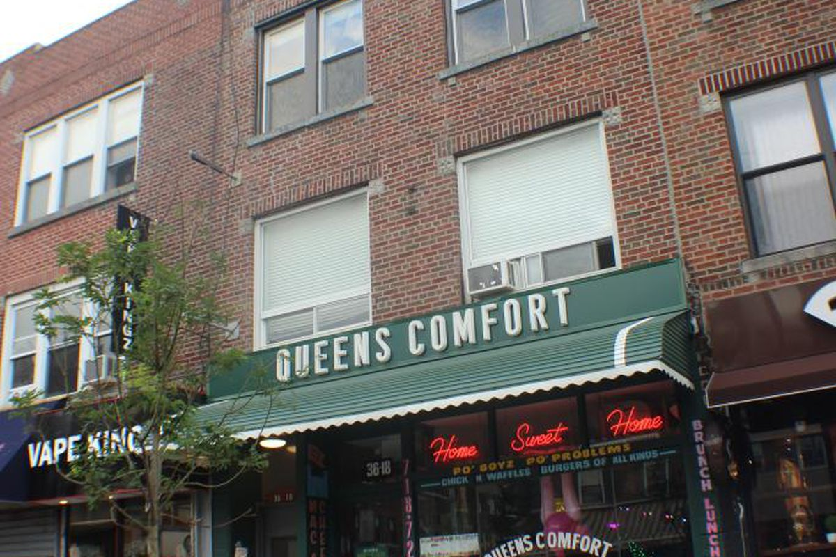 The exterior of a restaurant with the words Queens Comfort etched onto a green awning