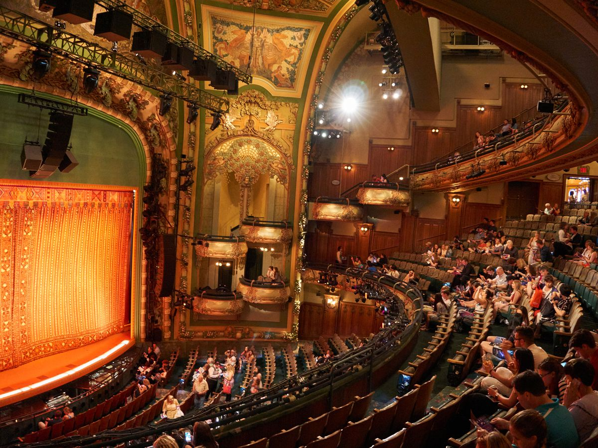 The New Amsterdam Theater in New York City. There are rows of seats, a stage with an orange curtain, and stage lights. The walls are decorated in ornamental design.