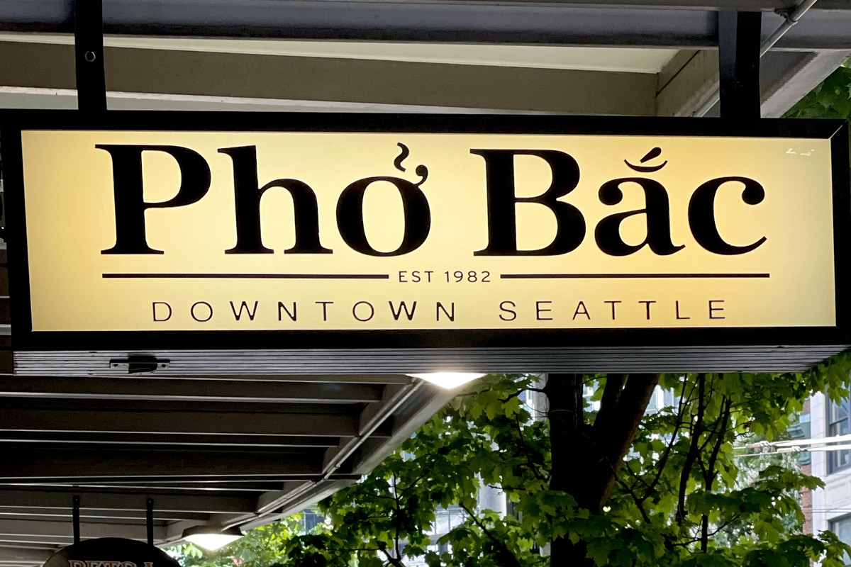 The glowing yellow sign for Pho Bac has the restaurant's name in bold letters, then below it (smaller) it says EST. 1982, Downtown Seattle.