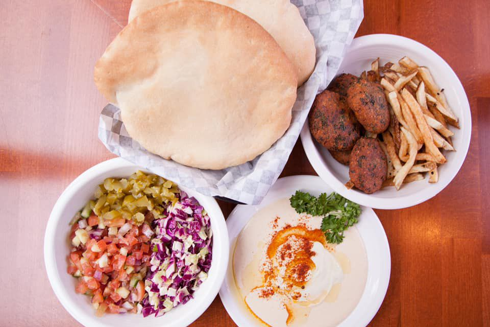An overhead view of a pita with hummus, falafel, and fries on the side