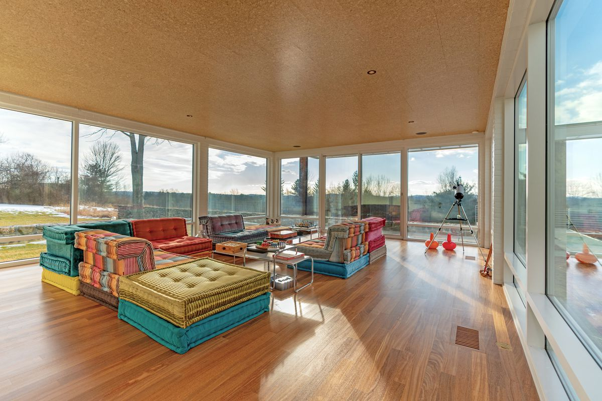 A glass-walled sitting room has wood floors and oversized couches in yellow, pink, and turquoise.