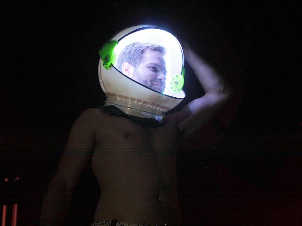 A shirtless man in a light-up helmet strikes a pose.