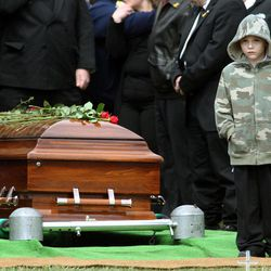 Nicholas Weichel, son of Rhode Island National Guard Sgt. Dennis Weichel Jr., who was killed in Afghanistan, stands next to his father's casket during funeral services at the state Veterans Cemetery in Exeter, R.I., Monday, April 2, 2012.   Weichel Jr., was struck and killed by an armored vehicle March 22 in Afghanistan while saving an Afghan boy.