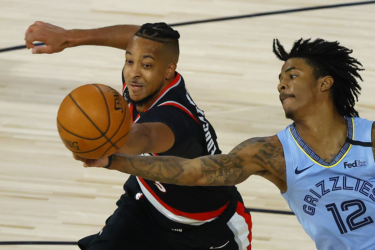 CJ McCollum of the Portland Trail Blazers and Ja Morant of the Memphis Grizzlies go after a rebound during the fourth quarter in the Western Conference play-in game one at The Field House at ESPN Wide World Of Sports Complex on August 15, 2020 in Lake Buena Vista, Florida.
