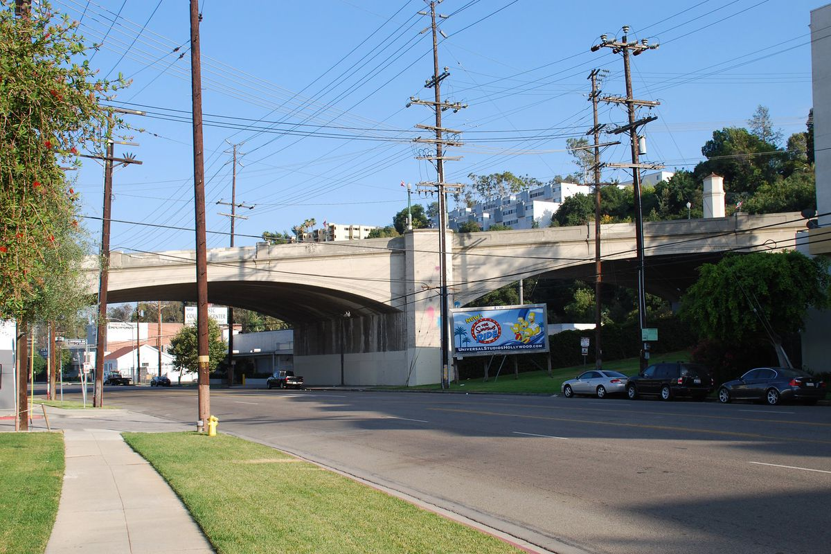 A bridge crossing over a road. Along the feet of the bridge are commercial spaces and grassy lots.