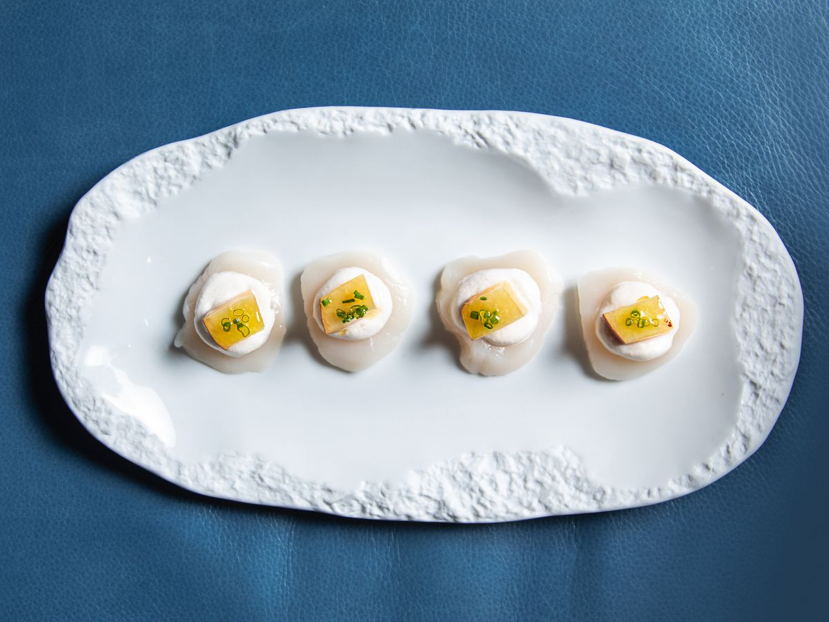 A white ceramic platter with scallop crudo topped with slices of mango.