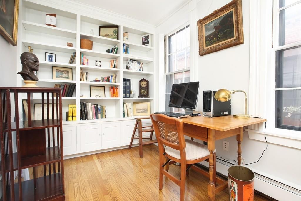 An upstairs office area with a desk and built-in bookshelves.