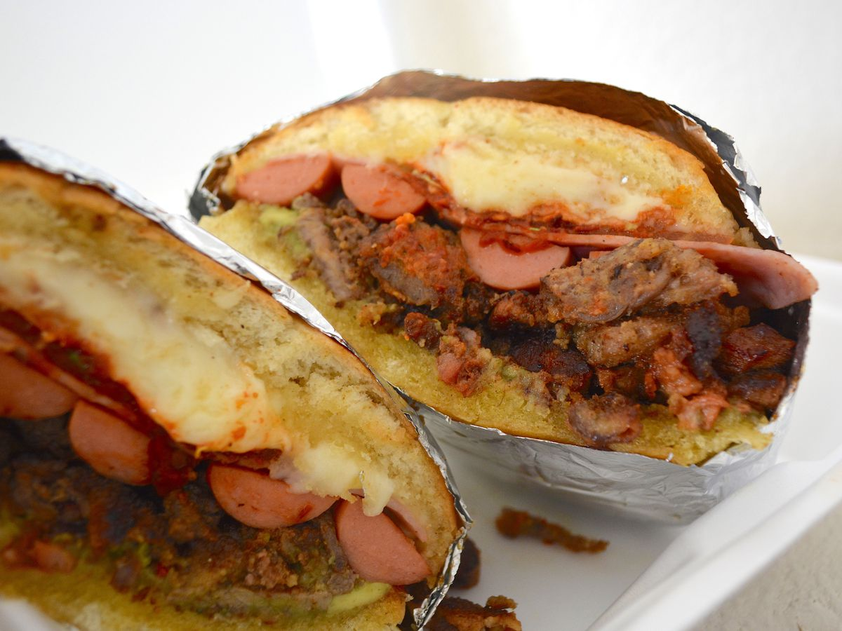 Torta Cubana with diced beef, breaded steak, marinated pork, ham, and hot dogs