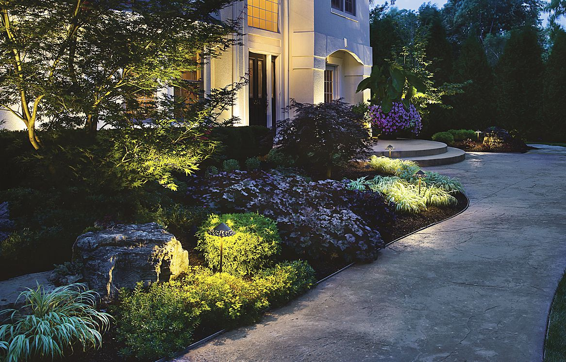 """<p>Instead of showcasing the property's concrete work, the fixtures in this layout let the lush greenery beside the walk lead the way.</p> <p><strong>Shown:</strong>Kichler 15871 Tannery Bronze Hammered Roof Light, about $145;<a href=""""http://www.lightingdirect.com/"""" target=""""_blank"""">lightingdirect.com</a></p> <script type=""""text/javascript""""> amzn_assoc_placement = """"adunit0""""; amzn_assoc_search_bar = """"true""""; amzn_assoc_tracking_id = """"hisldousent-20""""; amzn_assoc_ad_mode = """"manual""""; amzn_assoc_ad_ty"""