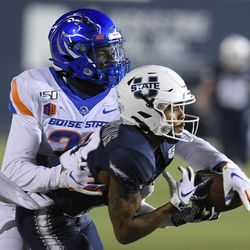 Utah State wide receiver Deven Thompkins (13) catches a pass as Boise State safety JL Skinner (33) defends during the first half of an NCAA college football game Saturday, Nov. 23, 2019, in Logan, Utah.