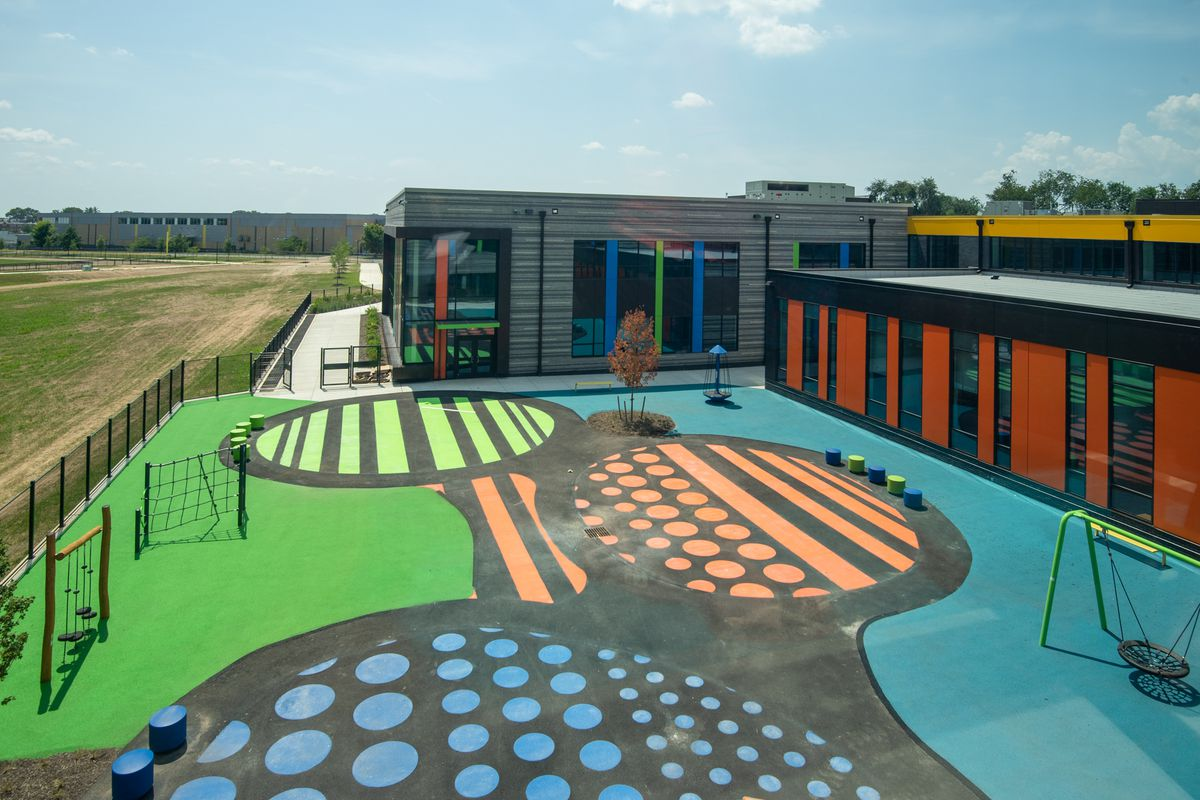 The courtyard of the new Northeast Community Propel Academy has bright green, orange, and blue floors and recess equipment.