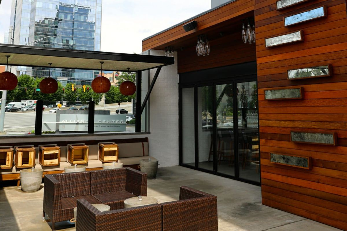 The outdoor patio with two couches, bar seating, and a wood wall with flower boxes at Little Alley Steak Buckhead, Atlanta