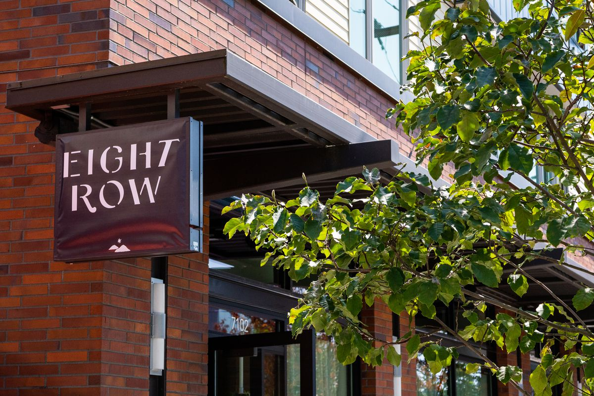 The sign outside Eight Row with the restaurant's name next to a tree.