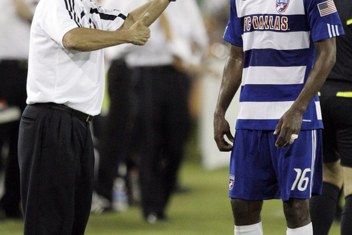 HOUSTON - MAY 05:  Head coach Schellas Hyndman of FC Dallas gives Atiba Harris instructions during an injury break in play against the Houston Dynamo at Robertson Stadium on May 5, 2010 in Houston, Texas.  (Photo by Bob Levey/Getty Images)