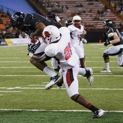 Hawaii wide receiver Darius Bright pulls in a touchdown pass over Lamar defensive back Branden Thomas during the second quarter of the NCAA game between the Lamar and Hawaii, Sept. 15, 2012 in Honolulu.