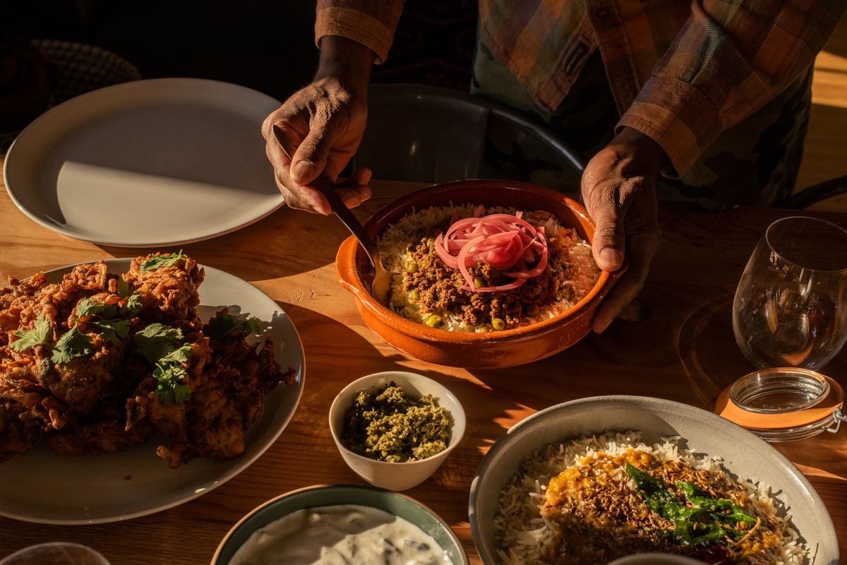 A selection of dishes from pop-up Karachi Cowboys on a table; one man in a flannel shirt presents a plate of kheema over rice with pickled onions on top