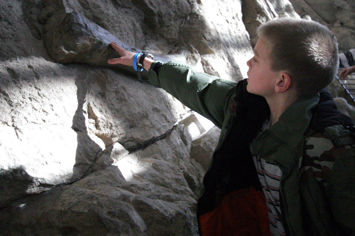 Hayden Bytendorp of South Jordan touches a dinosaur fossil embedded in the quarry wall at Dinosaur National Monument.