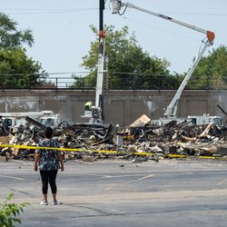 A person passes by what used to be the Department of Corrections building Tuesday afternoon, Aug. 25, 2020. The building was set on fire following the shooting of Jacob Blake by a police officer in Kenosha Sunday.