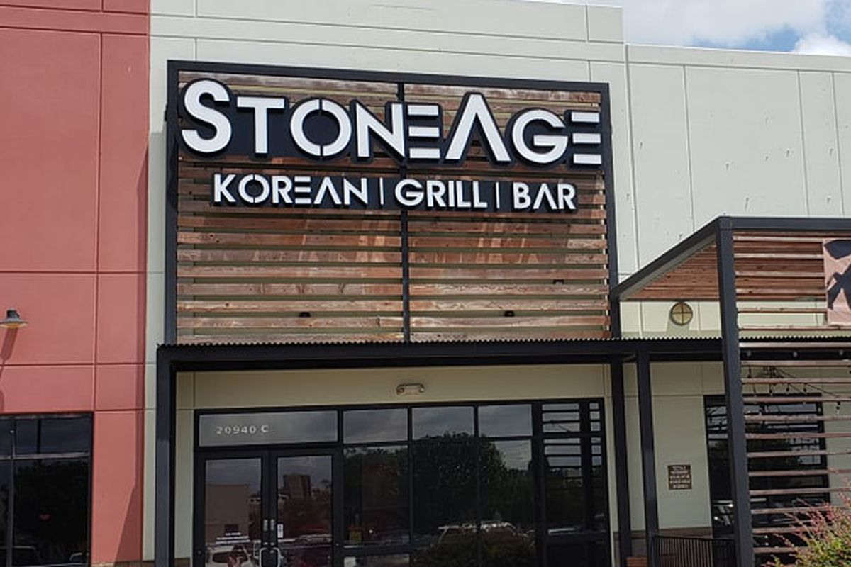 the exterior of a restaurant in a strip mall with a sign that reads Stone Age Korean Grill Bar