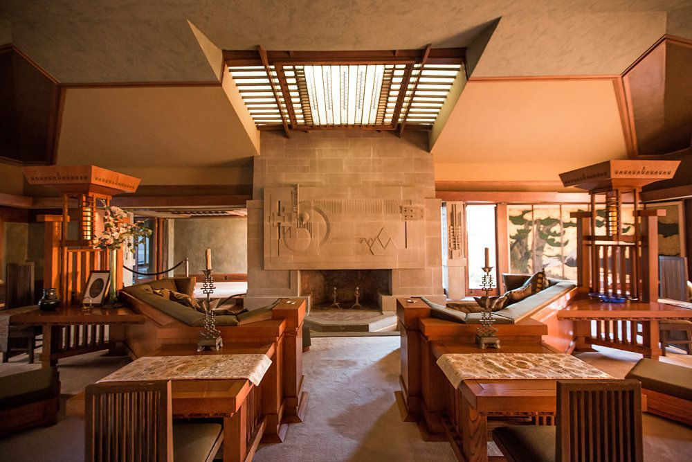 The Hollyhock House by Frank Lloyd Wright. The interior has couches, tables, a fireplace, and a skylight with wooden slats. The wall above the fireplace is brown brick. There is a tan floor.