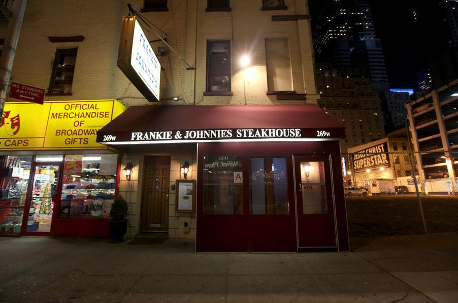 """A red awning is illuminated at night with the words: """"FRANKIE & JOHNNIE'S STEAKHOUSE"""""""