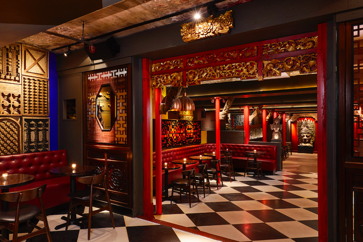 The interior of a lounge with red, gold, and wooden accents and a checkered black and white floor