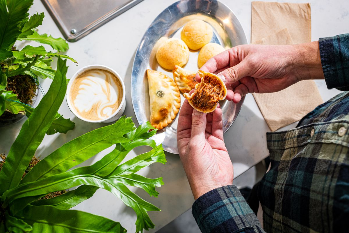 A pair of hands splits open an empanada to reveal a pulled pork filling at Lost Sock Coffee