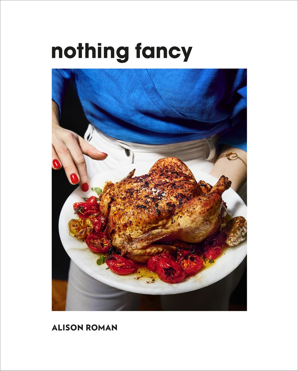 """Cover of """"Nothing Fancy"""" cookbook, with white border and cropped photo of a white woman, in white jeans and blue top, touching a plate of roast chicken with her red nail polish-coated fingers"""
