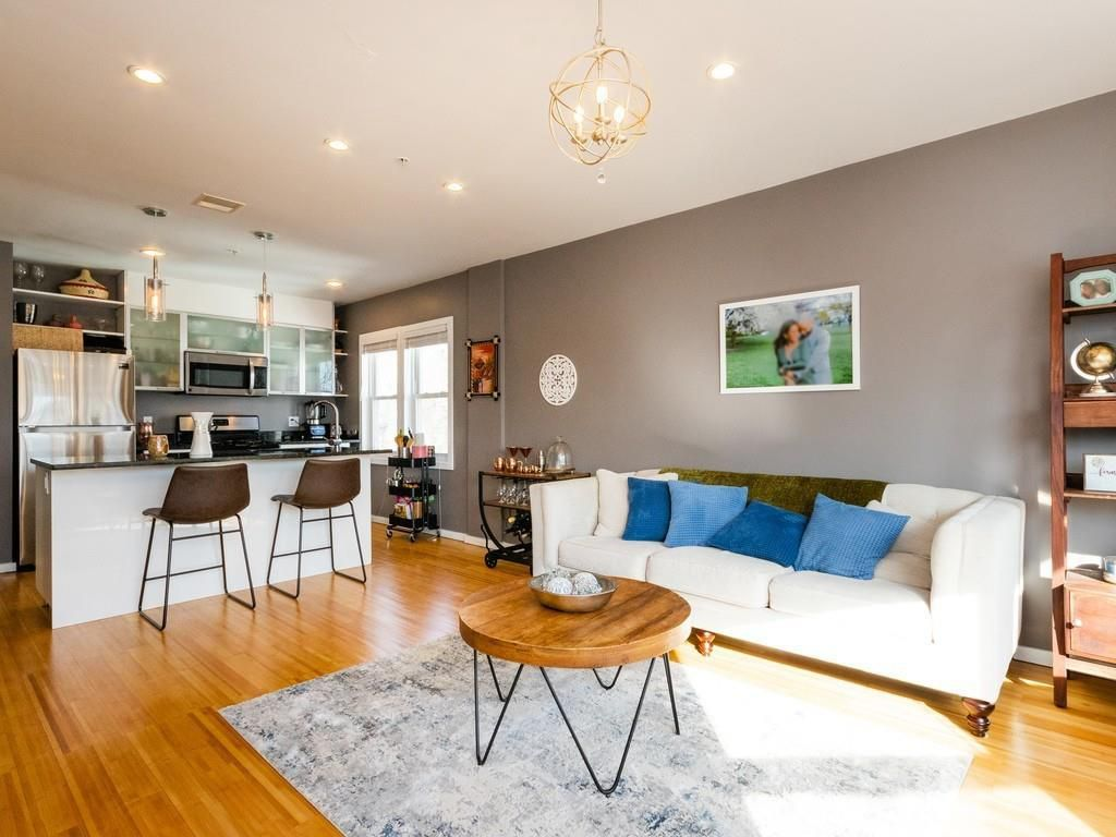 An open living room-kitchen area with stools in front of the counter separating them.