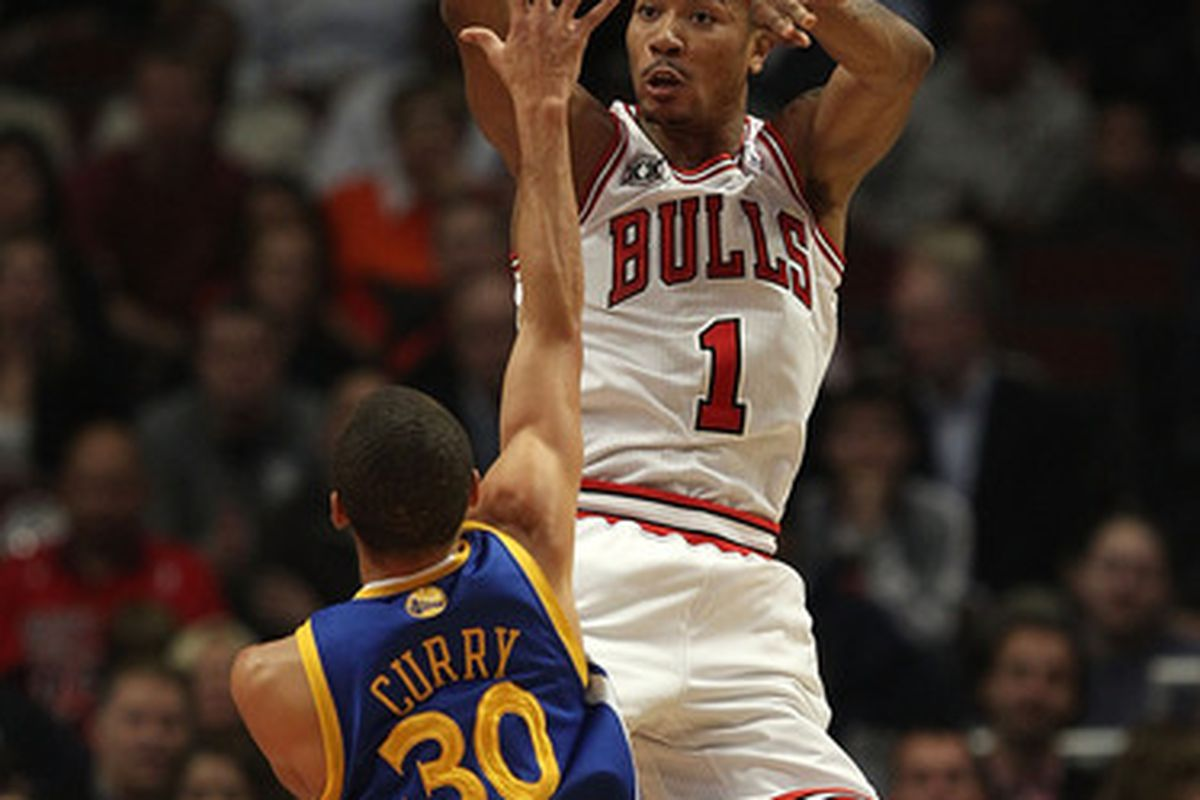 Derrick Rose of the Chicago Bulls leaps to pass the ball over Stephen Curry of the Golden State Warriors at the United Center on November 11 2010 in Chicago Illinois. (Photo by Jonathan Daniel/Getty Images)
