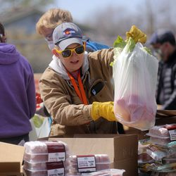 Emmalee Christensen bags food from the Utah Food Bank to hand out in the parking lot of a chapel belonging to The Church of Jesus Christ of Latter-day Saints in Taylorsville on Monday, April 13, 2020. The Utah Food Bank estimates it provided food to around 400 families at this location.