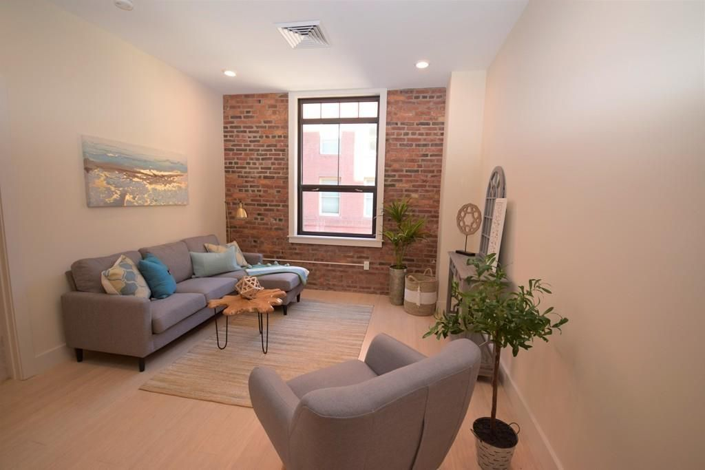 A small, square living room with furniture and a single brick wall.