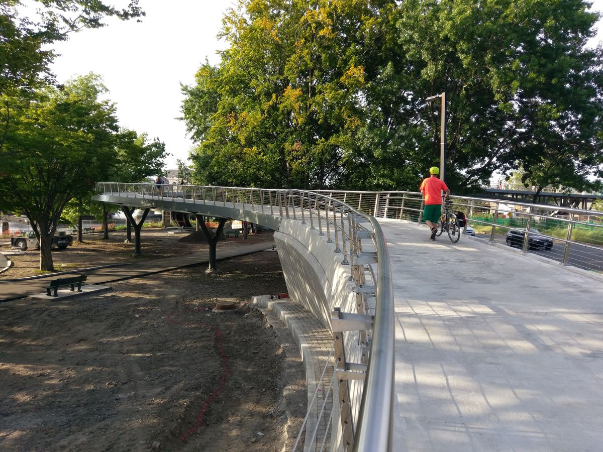 A steel pedestrian bridge over a park in a city, with people on the bridge.