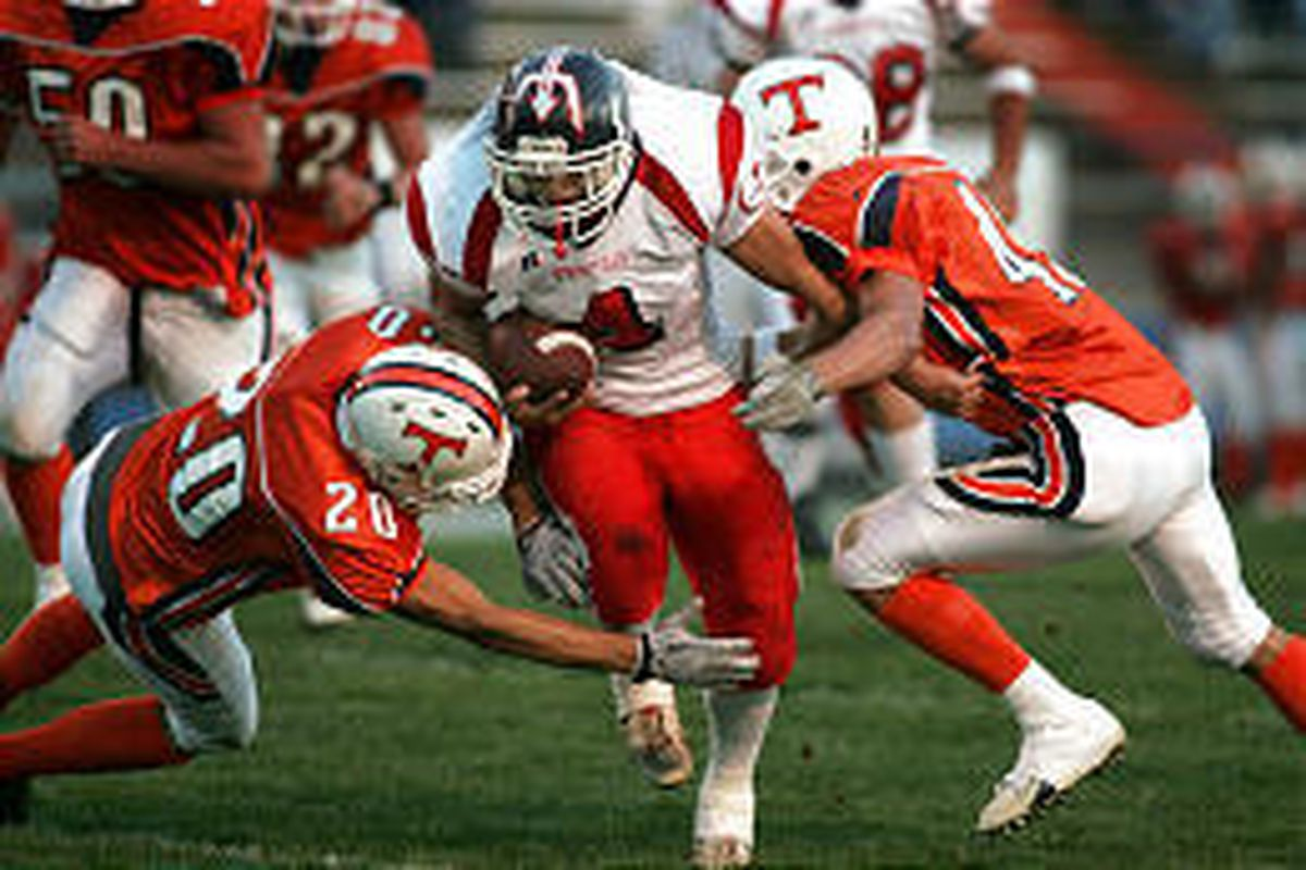 Springville's Trevyn Smith eludes Timpview's Dave Jackson (20) and Greg Atkinson, aiding the Devils' 465 total yards.
