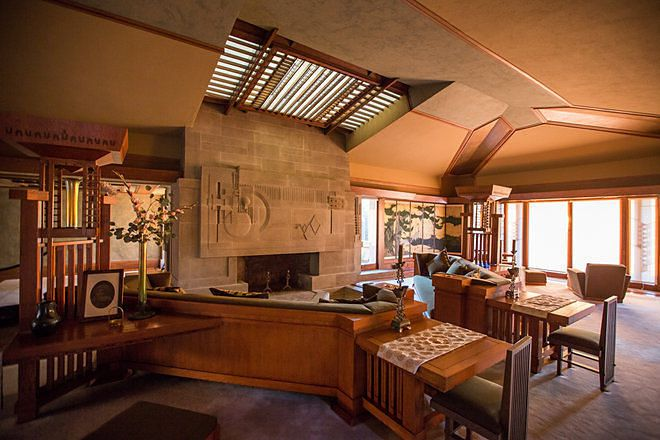 The interior of the Frank Lloyd Wright Hollyhock House. There is a skylight, tables, couch, and a fireplace.