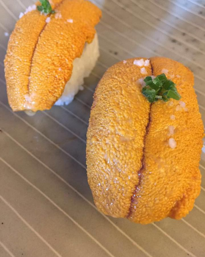 From above, a close-up on raw sea urchin topped with small herbal garnish and flakes of salt